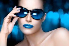 Πρότυπη γυναίκα μόδας στα μπλε μεγάλου μεγέθους γυαλιά ηλίου Ζωηρόχρωμο Makeu Στοκ Φωτογραφία