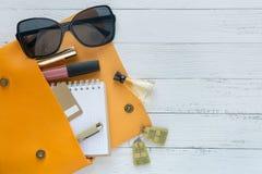 Έννοια μόδας Θηλυκά πράγματα, καλλυντικά προϊόντα, sunglass, σημειωματάριο και πορτοκαλιά τσάντα στο ξύλινο υπόβαθρο με το copysp στοκ φωτογραφία με δικαίωμα ελεύθερης χρήσης