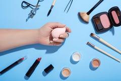 Makeup και θηλυκό σφουγγάρι εκμετάλλευσης χεριών makeup στο μπλε υπόβαθρο Στοκ εικόνα με δικαίωμα ελεύθερης χρήσης