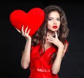 makeup Όμορφο κορίτσι brunette στο κόκκινο με το δώρο καρδιών για Valen Στοκ Φωτογραφία