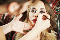 Makeup. Artist applying mascara on the eyelashes of a beautiful girl Royalty Free Stock Photo