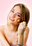Όμορφη νέα γυναίκα που βάζει στο makeup πέρα από μια ρόδινη ανασκόπηση Στοκ φωτογραφία με δικαίωμα ελεύθερης χρήσης