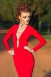 Το όμορφο κομψό κορίτσι με το όμορφο makeup και η τρίχα ένα κόκκινο βράδυ ντύνουν στο πάρκο Στοκ φωτογραφία με δικαίωμα ελεύθερης χρήσης