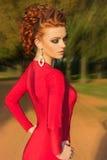 Το όμορφο κομψό κορίτσι με το όμορφο makeup και η τρίχα ένα κόκκινο βράδυ ντύνουν στο πάρκο Στοκ εικόνα με δικαίωμα ελεύθερης χρήσης