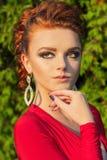 Το όμορφο κομψό κορίτσι με το όμορφο makeup και η τρίχα ένα κόκκινο βράδυ ντύνουν στο πάρκο Στοκ Εικόνες