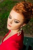 Το όμορφο κομψό κορίτσι με το όμορφο makeup και η τρίχα ένα κόκκινο βράδυ ντύνουν στο πάρκο Στοκ Φωτογραφία