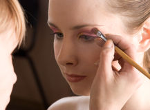 Makeup. Stylist causes make up the beautiful model Stock Image
