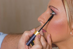 Makeup #8. Model receives professional makeup from Make-up artist stock photography
