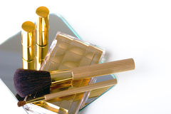 Makeup accessories in gold. Makeup accessories - brushes, lipsticks and eye shadow in golden covers on the mirror background Royalty Free Stock Photo