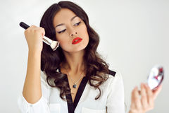 Makeup applying. Beautiful girl with cosmetic powder brush Stock Photos