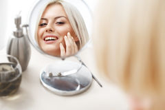 Makeup Applying. Beautiful Woman Looking at Her Face in the Mirror Stock Photo