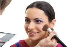 Makeup applying blusher to smiling model isolated Stock Photo