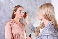 Makeup styling process with pro visagiste and model. Makeup applying process by professional artist wearing fashionable checkered oversized blazer jacket royalty free stock photos