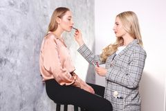 Makeup styling process with pro visagiste and model. Makeup applying process by professional artist wearing fashionable checkered oversized blazer jacket stock photo