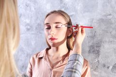 Makeup styling process with pro visagiste and model. Makeup applying process by professional artist wearing fashionable checkered oversized blazer jacket stock photos