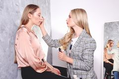Makeup styling process with pro visagiste and model. Makeup applying process by professional artist wearing fashionable checkered oversized blazer jacket stock photography