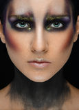 Makeup art and beautiful model theme: beautiful girl with a creative make-up black-and-purple and gold colors on a black backgroun stock image