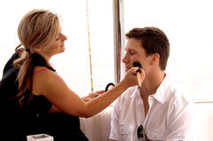 Makeup Artist. At work on a model on set Stock Photography