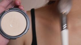 The makeup artist applies a beige powder foundation on the female face