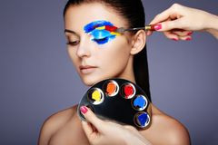 Makeup artist applies colorful makeup. Fashion model woman with colored face painted. Beauty art portrait of beautiful model with colorful abstract makeup Royalty Free Stock Photo