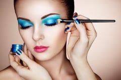 Makeup artist applies eye shadow Stock Images