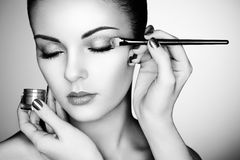 Makeup artist applies eye shadow. Beautiful woman face. Perfect makeup. Black and white Stock Images