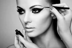 Makeup artist applies eye shadow. Beautiful woman face. Perfect makeup. Black and white photo Stock Photography