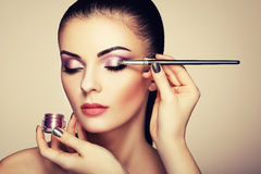 Makeup artist applies eye shadow. Beautiful woman face. Perfect makeup. Makeup detail. Beauty girl with perfect skin. Nails and manicure Royalty Free Stock Photos