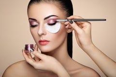 Makeup artist applies eye shadow Stock Photography