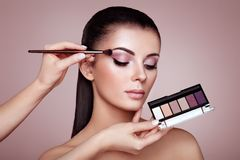 Makeup artist applies eye shadow. Beautiful Woman Face. Perfect Makeup. Make-up detail. Beauty Girl with Perfect Skin. Nails and Manicure. Eye Shadow Palette royalty free stock photo