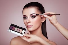 Makeup artist applies eye shadow Royalty Free Stock Images