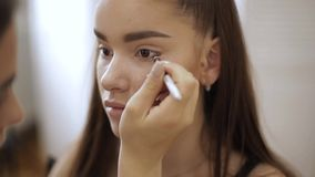 Makeup artist applies eye shadow, perfect evening makeup. Beauty redhead girl with perfect skin and freckles.  stock footage