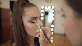 Makeup artist applies eye shadow, perfect evening makeup. Beauty redhead girl with perfect skin and freckles stock video footage
