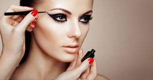 Makeup artist applies eyeshadow. Beautiful Woman Make-up Eye with Black Liner. Fashion Makeup Arrows. Red Nails Perfect Skin royalty free stock photo