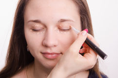Makeup artist applies foundation on eyelids Royalty Free Stock Photo