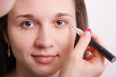 Makeup artist applies foundation on eyelids of young girl Royalty Free Stock Images