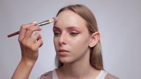 Makeup artist applies foundation on the face of a beautiful girl. Professional makeup concept