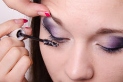 Makeup artist applies foundation under mascara on eyelashes Royalty Free Stock Photos