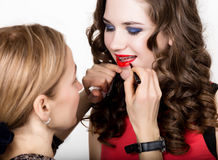 Makeup artist applies lipstick. Beautiful fashion woman face. Perfect makeup. Lipgloss brush. Stock Photo