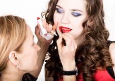 Makeup artist applies lipstick. Beautiful fashion woman face. Perfect makeup. Lipgloss brush. Royalty Free Stock Photography