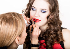 Makeup artist applies lipstick. Beautiful fashion woman face. Perfect makeup. Lipgloss brush. Royalty Free Stock Images