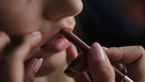 Makeup artist applies lipstick on beautiful lips Close-up stock video