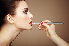 Makeup artist applies lipstick Stock Images