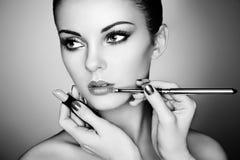 Makeup artist applies lipstick stock image