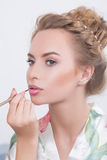Makeup artist applies lipstick. Beautiful woman Royalty Free Stock Photography