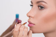Makeup artist applies lipstick. Beautiful woman Royalty Free Stock Photos