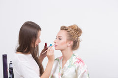 Makeup artist applies lipstick. Beautiful woman Stock Photos