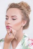 Makeup artist applies lipstick. Beautiful woman Stock Image
