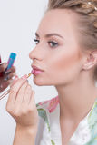 Makeup artist applies lipstick. Beautiful woman Stock Photography