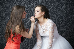 Makeup artist applies lipstick bride Royalty Free Stock Image